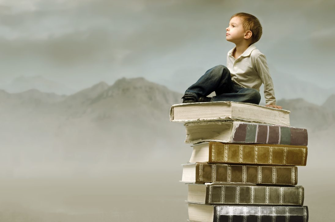 Child sitting on a stack of books in the mountains